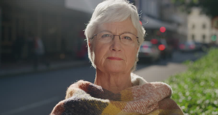Portrait of beautiful elderly woman looking calm pensive at camera wearing scarf middle aged caucasian female retirement age in urban city background real people series