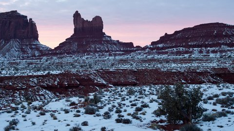 4K time lapse of pastel pink colored sunset clouds silhouetting snow covered spires, buttes and mesas geological rock formations in Monument Valley in Navajo Nation, Utah after a winter snow storm