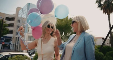 Excited fashionable senior female friends walking in the city, holding colorful balloons and celebrating