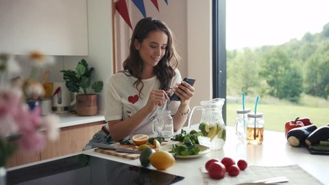 Attractive young woman in a casual outfit sits by the kitchen table, uses her smartphone, takes a glass jug with lemonade, pours it in cute mason jar. Smiling, happiness, relaxation. Female portrait