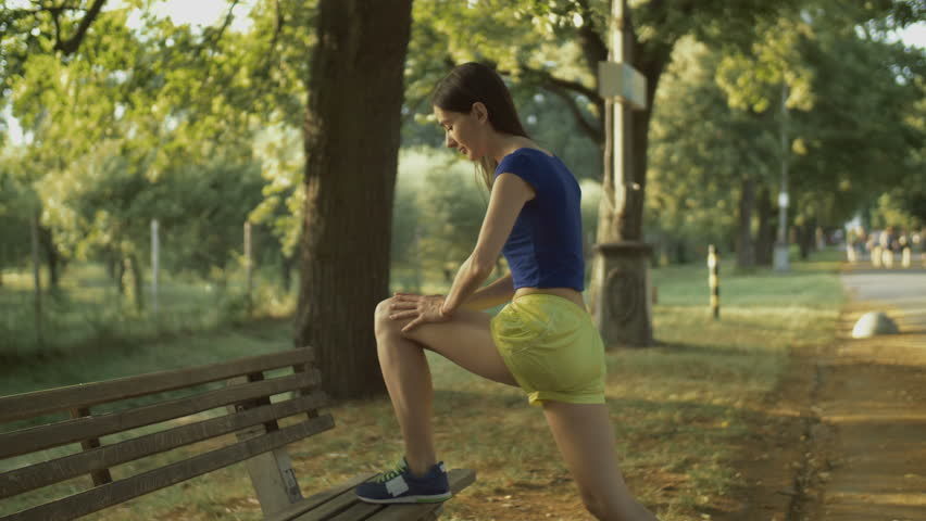 Beautiful fitness woman in sportswear stretching legs on bench, doing flexibility exercises before running workout in summer park. Healthy fit woman warming up in rays of setting sun before jogging. #1013039672
