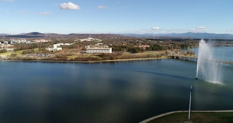 Recreational park on shores of lake Burley Griffin in Canberra between lake bridges from tall water fountain to distant waterfront of government district.