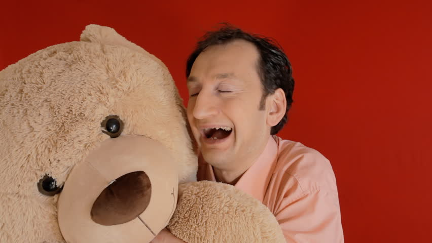 The friendship between a funny ugly man and a giant teddybear toy. Red background.