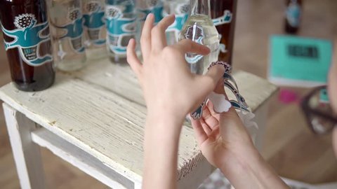 Close-up of a girl glues stickers on glass bottles with homemade alcohol. A transparent bottle of color stands on a white stool against the background of bottles, a room and a flower