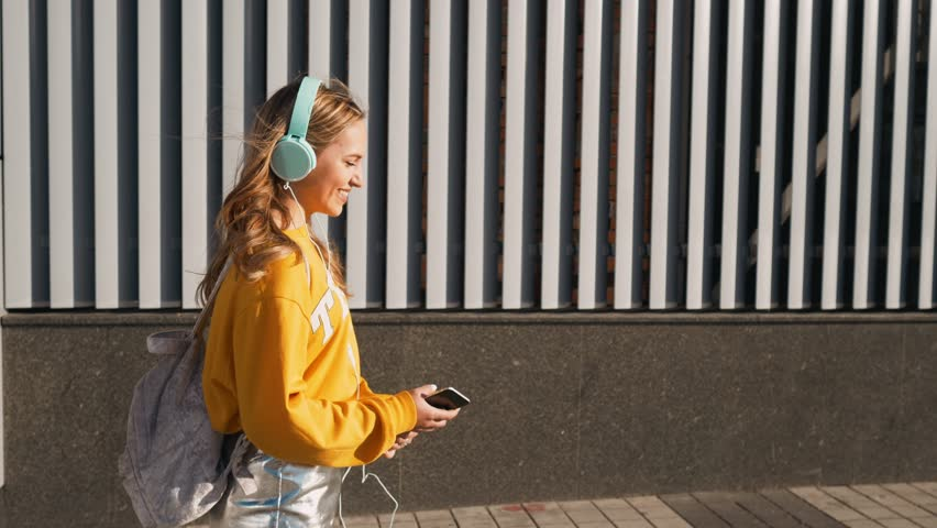 Portrait of young cute attractive young girl in urban background listening to music with headphones. Woman wearing yellow blouse and silver skirt. | Shutterstock HD Video #1013067572