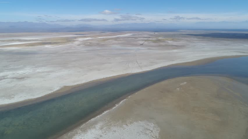 Aerial drone scene of Llancanelo lagoon in Malargüe, Mendoza, Argentina. Water reflection and white dry salty shore ground. Camera moving forwards towards a volcano. The Andes mountains on background
