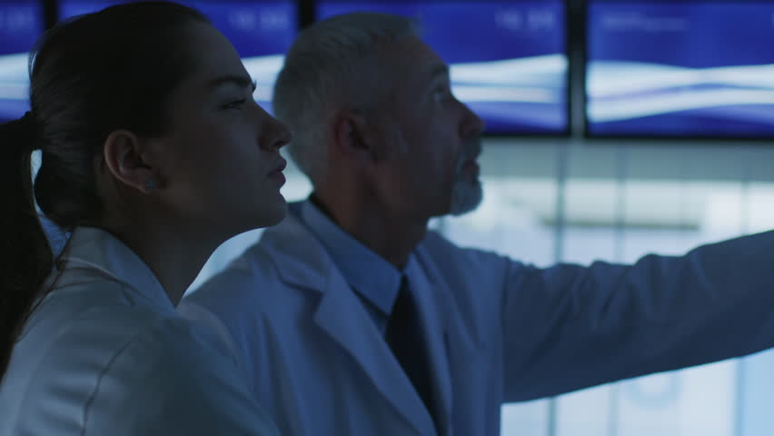 Close-up Shot of Two Medical Scientists / Neurologists, Talking and Pointing at TV Wall Monitor in the Modern Laboratory. Research Scientists Making New Discoveries in the fields of Neurophysiology.