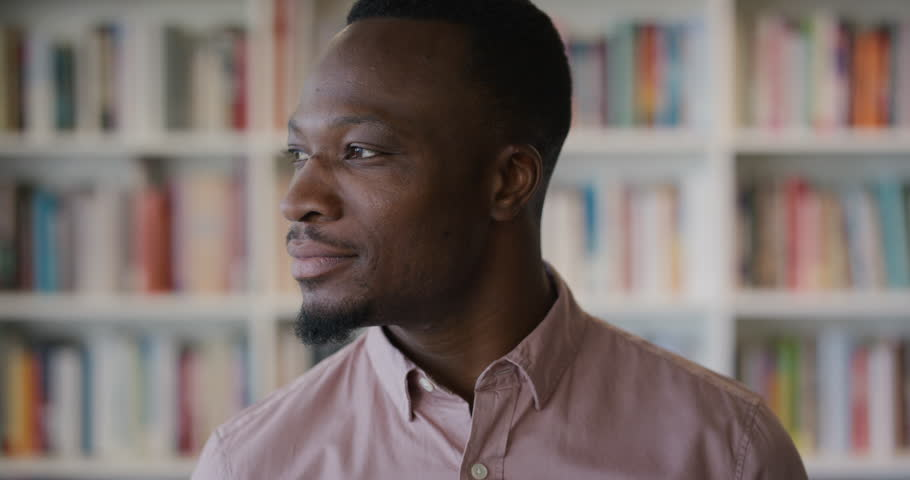 Portrait successful african american businessman turns head smiling enjoying professional lifestyle success in library bookshelf background slow motion