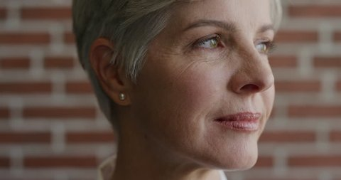Close up portrait of beautiful middle aged woman thinking, turns head
