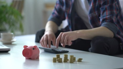 Man calculating money, putting coins into piggy bank, family budget planning