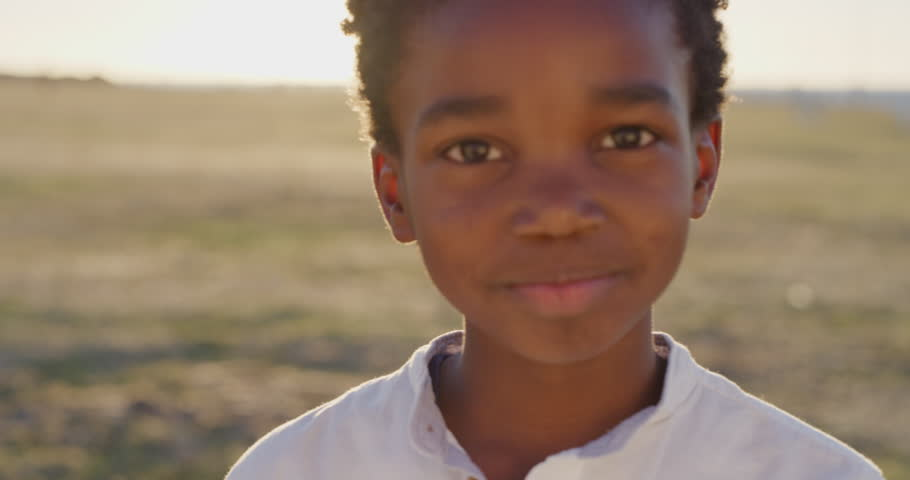 Close up portrait of cute african american boy smiling cheerful looking at camera happy enjoying sunny day at seaside park bright vibrant sunset real people series   Shutterstock HD Video #1013096612