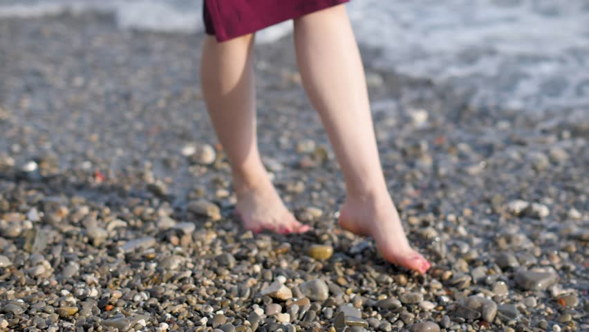 Woman bare feet walking along pebble beach and sea waves close up | Shutterstock HD Video #1013183792