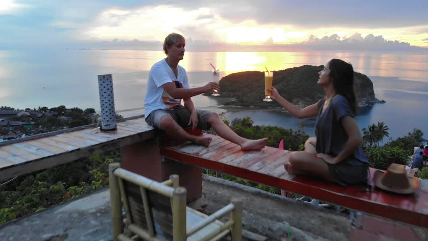 Young couple talking, raising toast with cocktails and admire sunset on terrace in cafe. View from drone flying to the sea in mountains on tropical island of Koh Phangan. 1920x1080