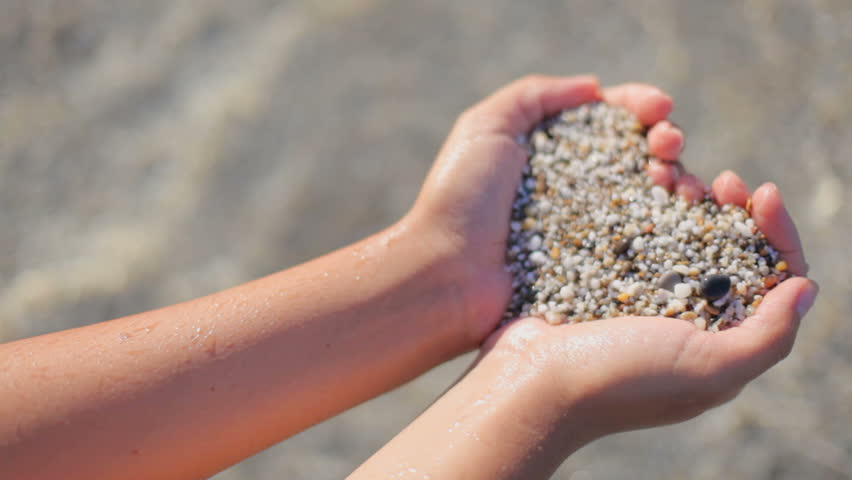The girl is holding a heart of sea sand in the background against the transparent sea water. The concept of a romantic summer holiday   Shutterstock HD Video #1013190452