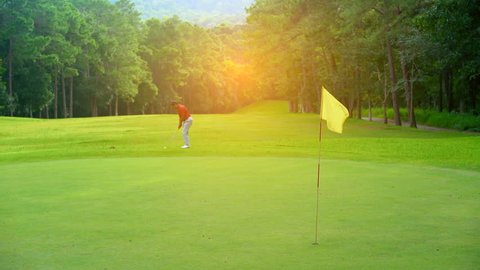Golf sport concept, Golfer slow motion chip golf ball to hole on green for the winner. Golf course is beautiful fairway and layout on nature tree on hills in open tournament. Yellow flag on green