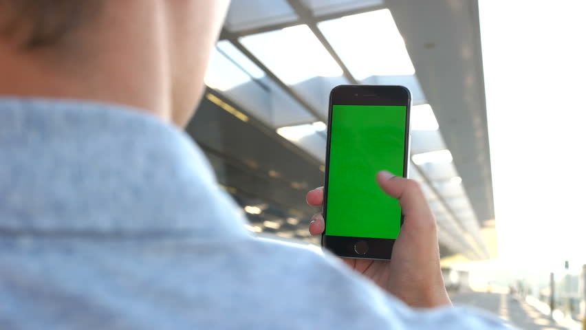 Close up shot of man hands holding smart phone with green screen on airport background. View from the back. Chroma key. | Shutterstock HD Video #1013198072
