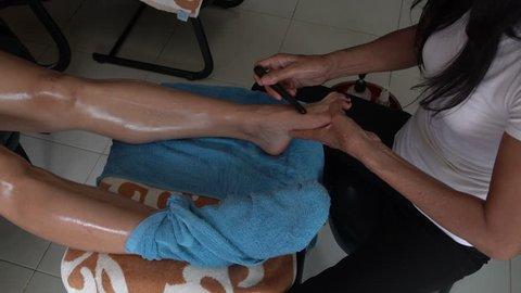 Thai foot massage using teak sticks for foot reflexology