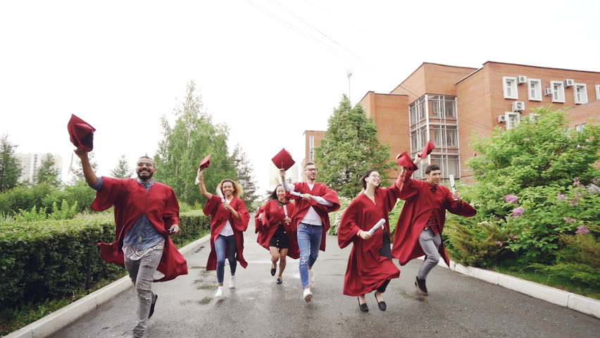 Slow motion of merry graduates running, holding diplomas and waving mortarboards enjoying freedom. Higher education, youth and happiness concept. | Shutterstock HD Video #1013212322