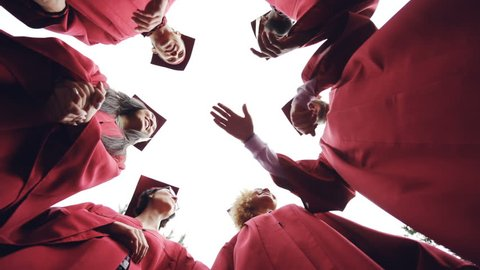 Low angle shot of graduating students putting hands together then raising them in the air and clapping hands, young people are wearing traditional gowns and hats.