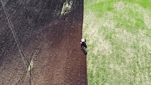 Tractor cultivating arable land for seeding crops, aerial view. Agricultural land