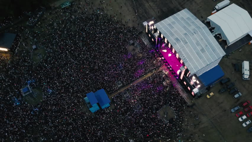 A large crowd of people at a music festival near the scene in the evening in the summer. Concert in the open air. Aerial view