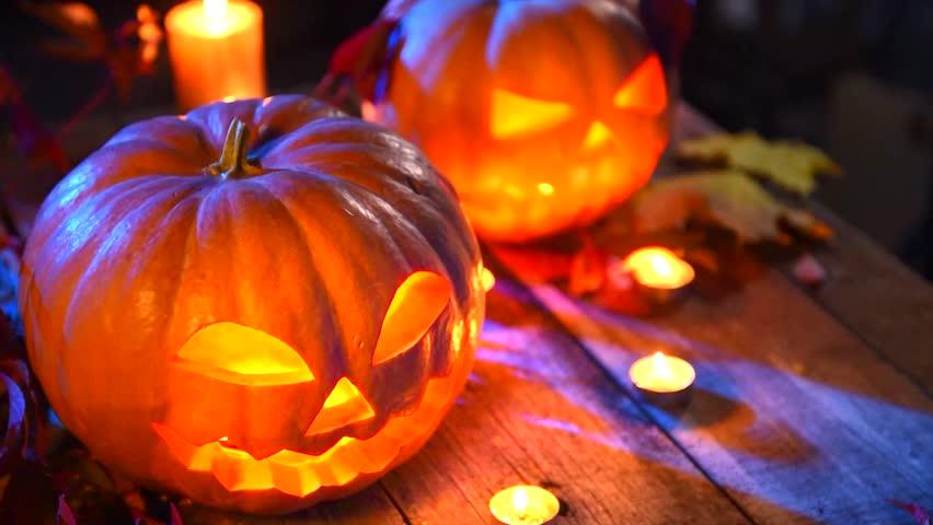 Halloween pumpkin head jack lantern with burning candles over black background. Halloween holidays art design, celebration. Halloween holiday night scene. 4K UHD video