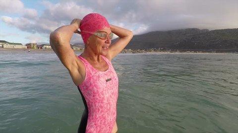 Senior woman preparing for early morning swim at the beach