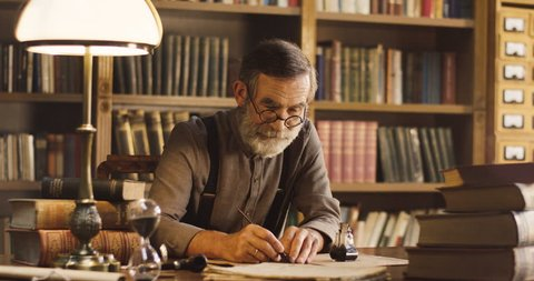 Portrait of the senior man writing on the old paper while sitting in the library room with ancient atmosphere, then thinking and having and idea.