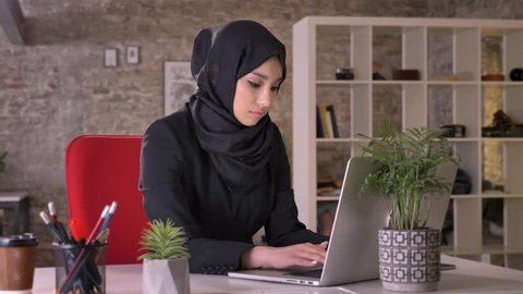 Young muslim girl in hijab is working with laptop in office, watching at camera, smiling, work concept