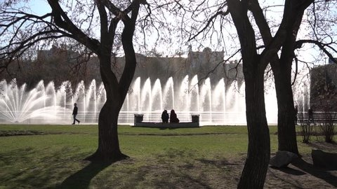 Two women on a wooden bench in the park on sunny day. Footage. People enjoying life, sitting on bench in park, looking at fountain. Back view. In front of them is a large pond with duckweed and