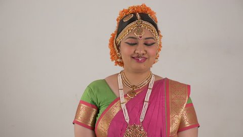 Indian girl showing different moods using traditional Bharat Natyam dance form. Smile expression.
