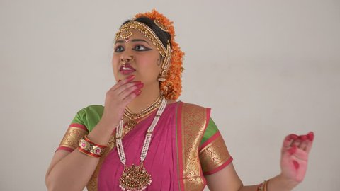 Indian girl showing different moods using traditional Bharat Natyam dance form. Pleased expression.