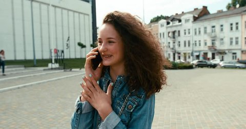 Attractive happy young girl with charming smile and braces is talking on the mobile phone while walking along the street.