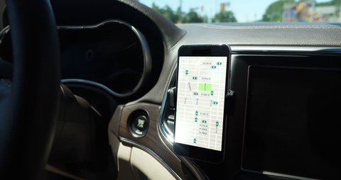 A smartphone attached to the dash on a vent holder in a moving car shows the traffic patterns of a ride sharing network. App screen simulated.