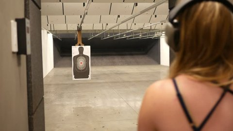 Woman shoots at a target of a man on an indoor gun shooting firing range