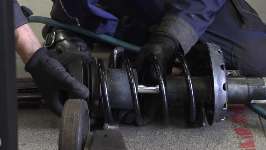 Automotive mechanic repairs shock absorber