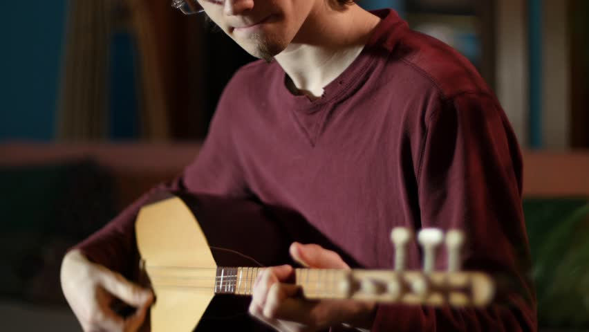 Closeup on the fingering on a beautifully lit saz being performed by a young man.