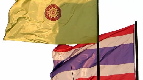 The dhammacakka flag, the symbol of Buddhism in Thailand and Flag of the Kingdom of Thailand flying in wind on sky.