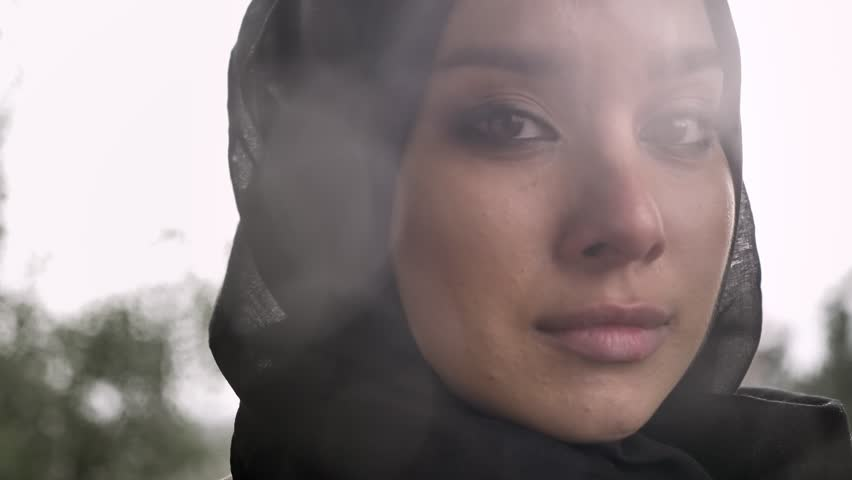 Portrait of young sad muslim woman in hijab looking at camera and crying, rainy weather in background | Shutterstock HD Video #1013416802