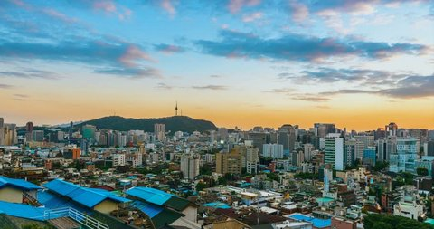 Sunset time lapse of Seoul downtown cityscape and Ewha wall painting village from day to night. Seoul, South Korea.