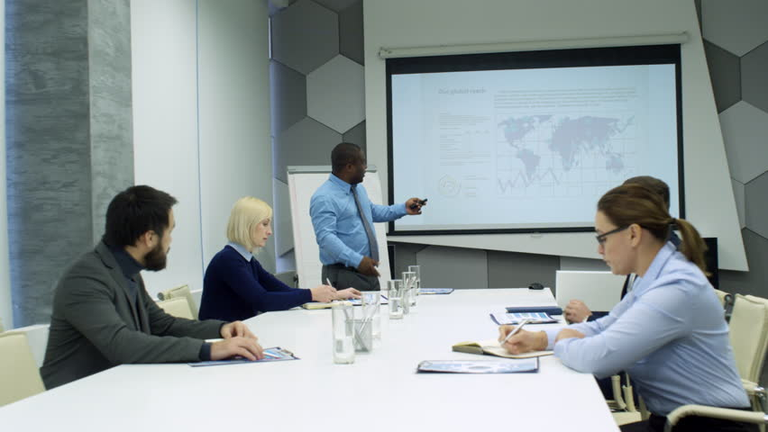 African american businessman standing at whiteboard and giving presentation to mixed raced colleagues in meeting room | Shutterstock HD Video #1013440952