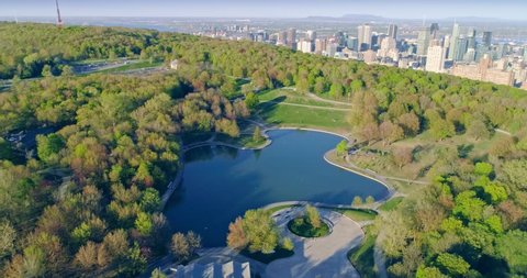 AERIAL: Flying over Beaver Lake at the top of Mont Royal with the city skyline visible in the distance. Montreal, Canada