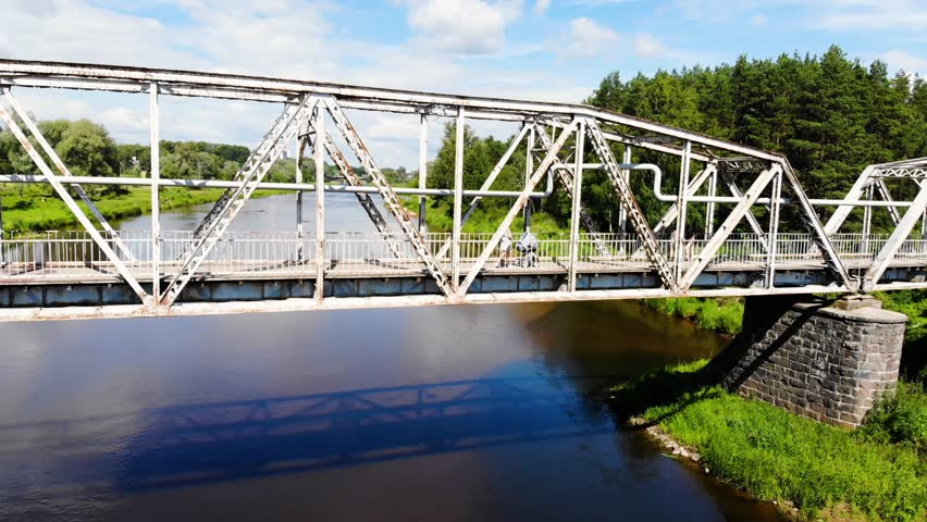 Drone footage of metal bridge over beautiful river while mother walking with baby strollers.
