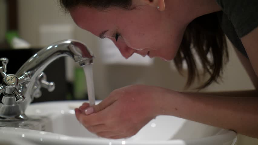 Woman splash water on face, stay over sink at washing room. Young adult lady feel tired at evening, closeup shot. She hold cupped hands then rise up to face