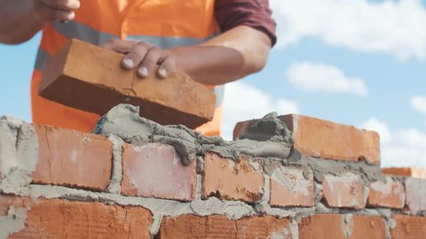 Close-up shut of Bricklayer working on a blue sky background