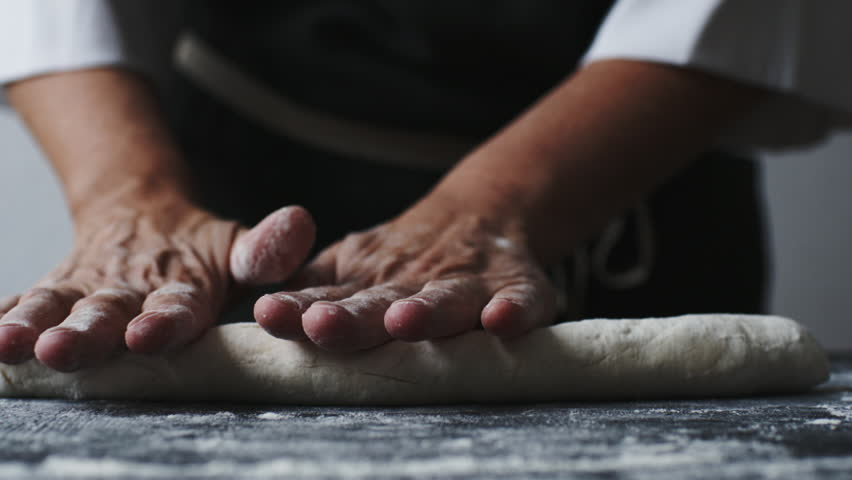 Woman rolling the dough by hands, slow motion at 240 fps #1013468102