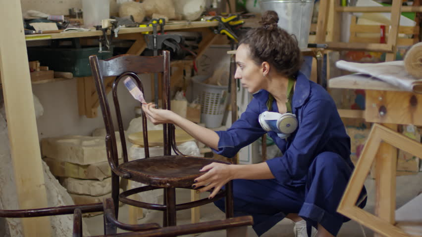 Concentrated young woman in workwear using paintbrush to apply varnish on brown wooden chair in carpentry workshop | Shutterstock HD Video #1013474312