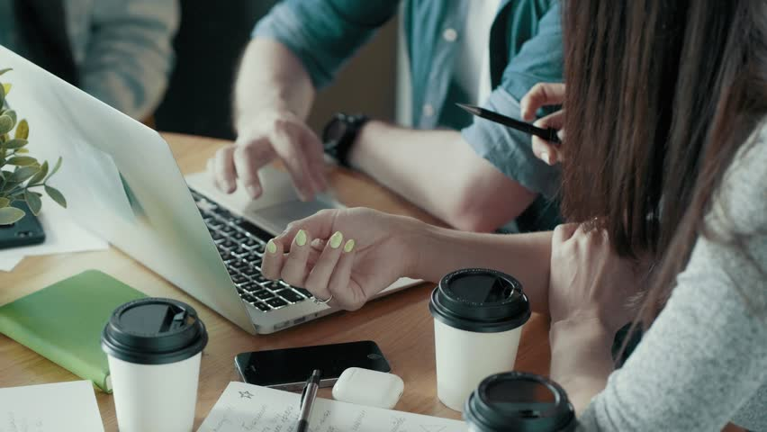 Workflow in modern start up office desk with devices papers documents coffee creative business team meeting brainstorming using digital display technology female hand pointing at laptop screen use pen | Shutterstock HD Video #1013484992