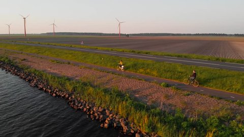 Couple enjoying a bicycle ride on a bike path along shore of Dutch polder Flevoland, with windmill park and fields on the background, at sunset.