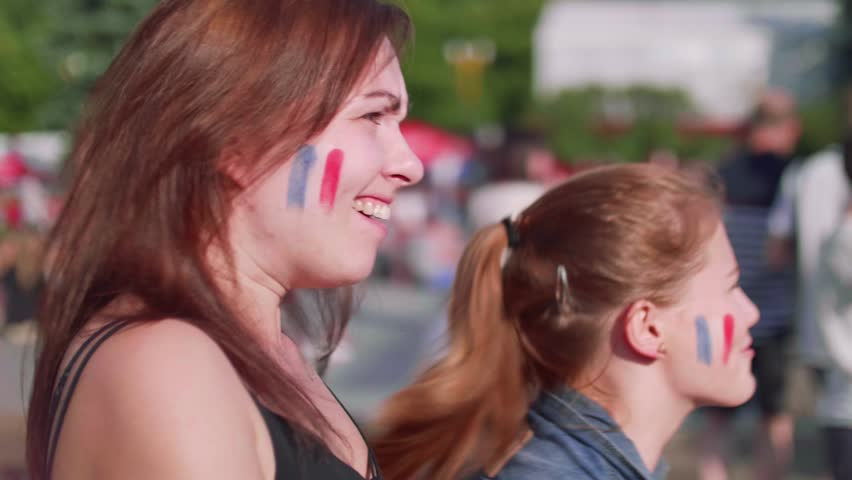 Happy girls watch game cheering for French team. Side view   Shutterstock HD Video #1013519882